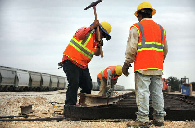 Contract workers from Alamo Railroad Inc. drive in rail spikes on a new section of track at Texas Gonzales and Northern Railway. Operations at the Texas Gonzales and Northern Railway, just outside of Gonzales, Texas have taken off due to the increased business from the Eagle Ford.  Tuesday, Nov. 13, 2012. Photo: Bob Owen, San Antonio Express-News / © 2012 San Antonio Express-News