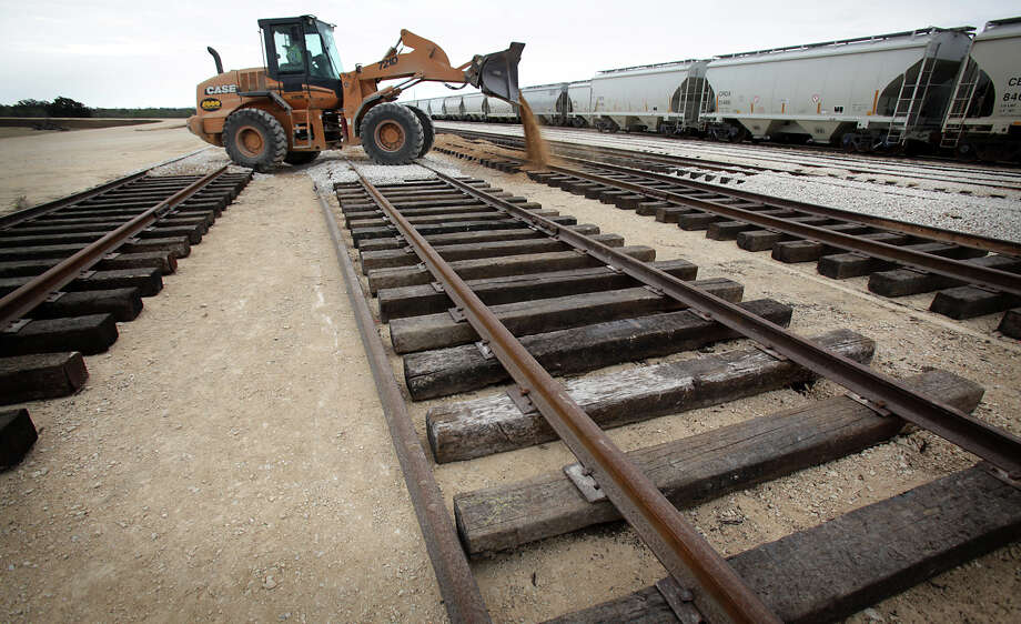 A front end loader operator spreads dirt on new sections of track at Texas Gonzales and Northern Railway.  Operations at the Texas Gonzales and Northern Railway, just outside of Gonzales, Texas have taken off due to the increased business from the Eagle Ford.  Tuesday, Nov. 13, 2012. Photo: Bob Owen, San Antonio Express-News / © 2012 San Antonio Express-News