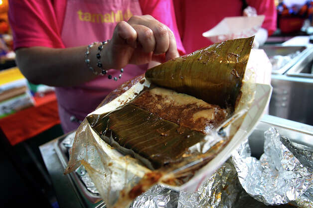A chicken mole tamal wrapped in banana leaf is offered by Tamalhi at the Country of 1100 Tamales at Pearl event on Saturday, Dec. 1, 2012. Thousands of visitors packed the Pearl to try tamales from 40 tamal makers who offered traditional and  innovative styles to satisfy every appetite. Photo: Kin Man Hui, Express-News / © 2012 San Antonio Express-News