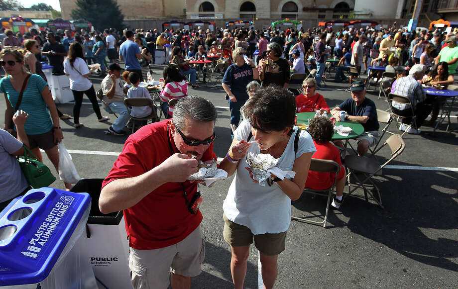 Jill Holbert (right) and Robert Baca from New Mexico enjoy a sampling of tamales at the Country of 1100 Tamales at Pearl event on Saturday, Dec. 1, 2012. The couple joined thousands of other visitors at the Pearl to try tamales from 40 tamal makers who offered traditional and  innovative styles to satisfy every appetite. Photo: Kin Man Hui, Express-News / © 2012 San Antonio Express-News
