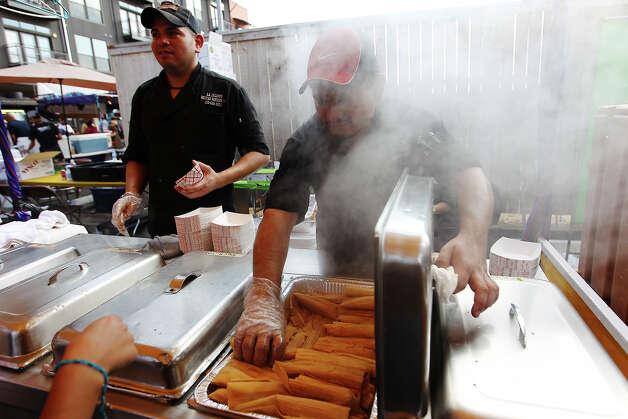 Albert Hernandez (center) of JJ Tamales gets a face full of steam as he opens a lid to fill an order of tamales at the Country of 1100 Tamales at Pearl event on Saturday, Dec. 1, 2012. Thousands of visitors packed the Pearl to try tamales from 40 tamal makers who offered traditional and  innovative styles to satisfy every appetite. Photo: Kin Man Hui, Express-News / © 2012 San Antonio Express-News
