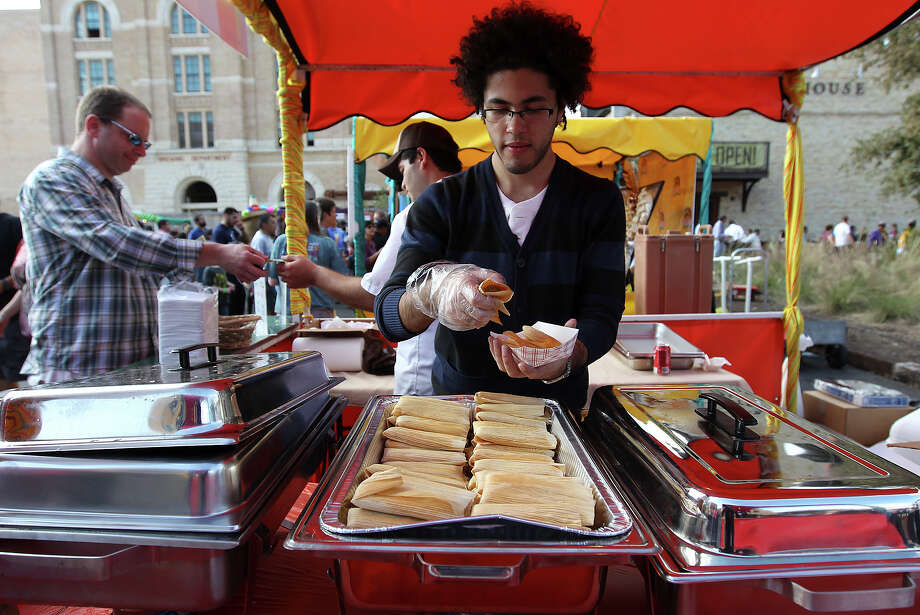 Iker Flores of La Hacienda serves up tamales at  the Country of 1100 Tamales at Pearl event on Saturday, Dec. 1, 2012. Thousands of visitors packed the Pearl to try tamales from 40 tamal makers who offered traditional and innovative styles to satisfy every appetite. Photo: Kin Man Hui, Express-News / © 2012 San Antonio Express-News