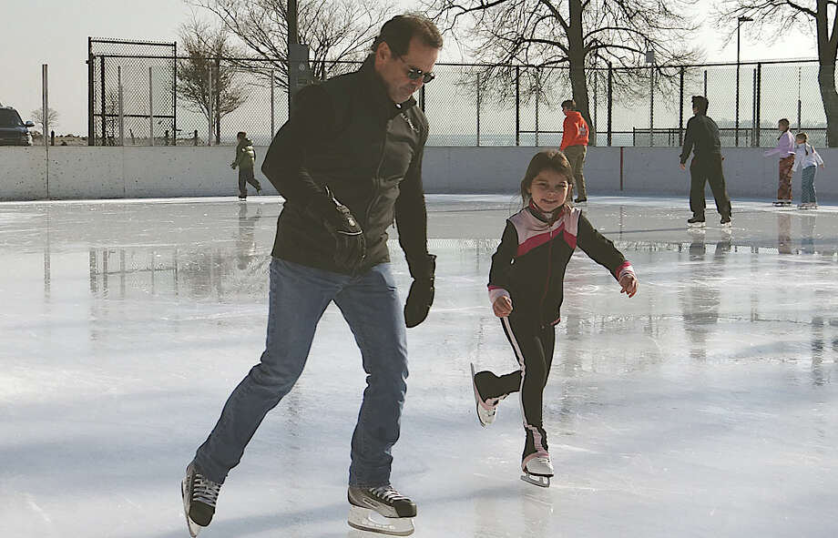Louis  DeFrancesco and daughter Dakota enjoy the first day of skating Friday at the Westport PAL rink at Longshore. Photo: Mike Lauterborn / Westport News contributed