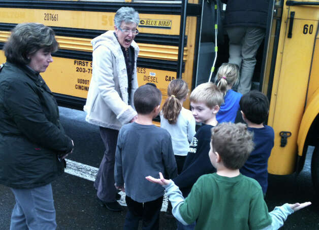 Osborn Hill School students board a bookmobile Tuesday under the guidance of Karen Cooney, left, a library media paraprofessional, and Denise Rehder, the school's library media specialist. The school's library has been closed since the discoverry of PCBs on the premises. Fairfield CT 11/27/12 Photo: Andrew Brophy / Fairfield Citizen contributed