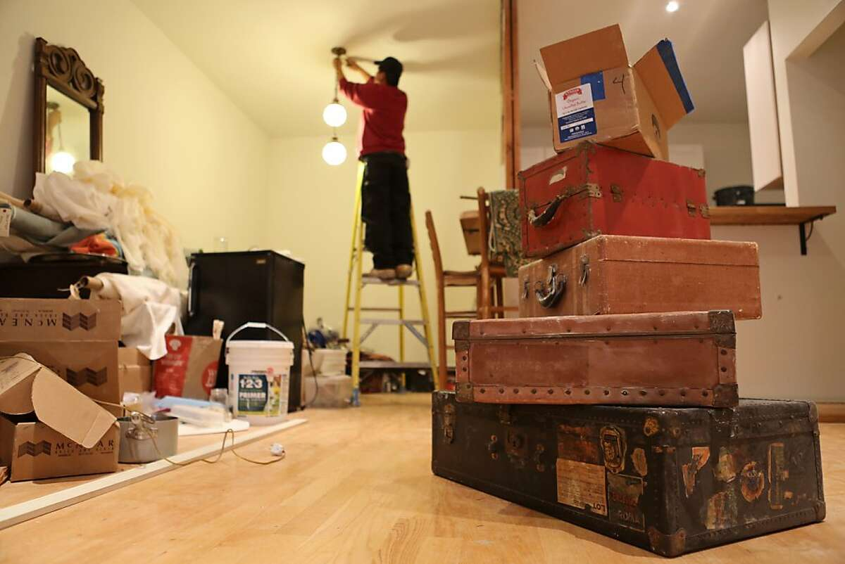 Boxes line the walls and floors of Karen Rogers condo during renovations, while Bao, a hired construction worker, adjusts recently installed light fixtures. Karen Rogers, 25, used to live in a big group house in Berkeley for the first couple of years after college but now has saved enough money to buy her own condo in Oakland. According to the Census Bureau, as the economy is recovering, people are beginning to feel confident to commit to having their own place.