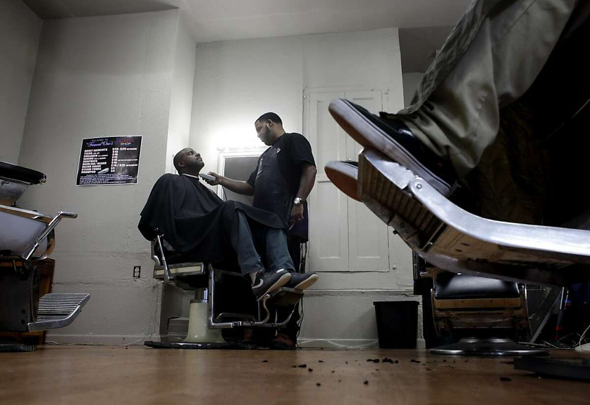 Robeson Perry, owner of Famous One's Barber Shop cuts Kenyatta Rowe hair, Friday November 30, 2012, in Oakland, Calif.