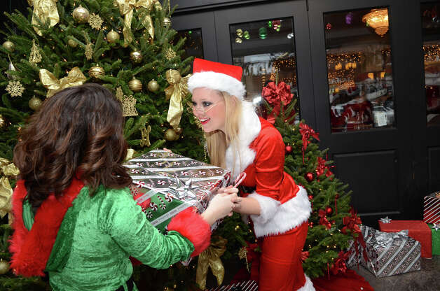 Alexanda Maksimow, of Stamford, hands a present to Eryn Wassa, of Southbury in front of Butterfield8 on Bedford Street in Stamford during the annual Stamford SantaCon pub crawl on Saturday, Dec. 1, 2012. Photo: Amy Mortensen / Connecticut Post Freelance