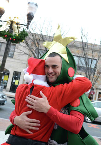 Anthony Giuliano, of West Chester, smiles as he is approached and hugged by a complete stranger, Jeff Rothband, of New Haven, on Bedford Street in Stamford during the annual Stamford SantaCon pub crawl on Saturday, Dec. 1, 2012. Photo: Amy Mortensen / Connecticut Post Freelance