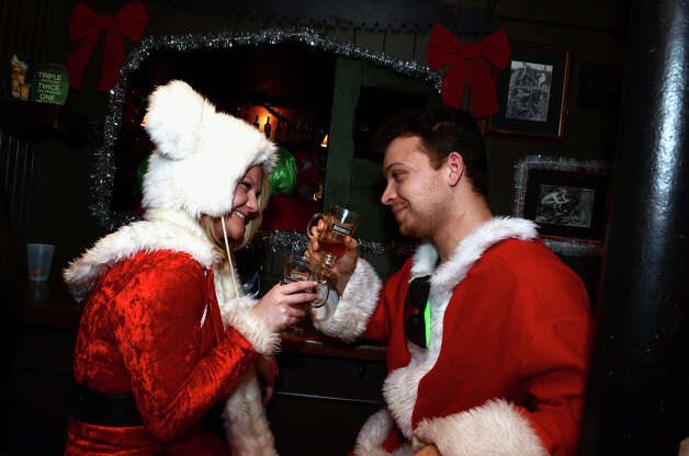 Kara O'Connor, of Norwalk, enjoys a drink at the bar with Joe Melfi, also of Norwalk, at Tigin on Bedford Street in Stamford during the annual Stamford SantaCon pub crawl on Saturday, Dec. 1, 2012. Photo: Amy Mortensen / Connecticut Post Freelance
