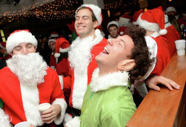 Chris Polizois, of Stamford, dressed as an elf, cocks his head back in laughter with friends John Tabor and Ben Jessen while at Butterfield8 on Bedford Street in Stamford during the annual Stamford SantaCon pub crawl on Saturday, Dec. 1, 2012. Photo: Amy Mortensen / Connecticut Post Freelance
