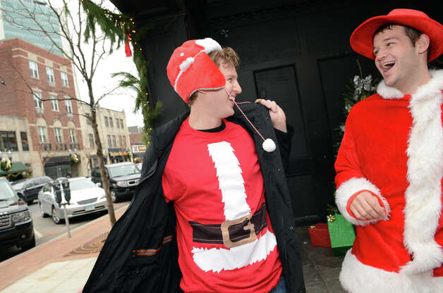 Mike Zarolinski, of Stamford, pulls off his coat to reveal his Santa-themed shirt to friend, Chris Gradel, of Stamford, outside of Butterfield8 on Bedford Street in Stamford during the annual Stamford SantaCon pub crawl on Saturday, Dec. 1, 2012. Photo: Amy Mortensen / Connecticut Post Freelance