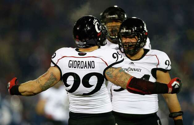 EAST HARTFORD, CT - DECEMBER 1: Dan Giordano #99 of the Cincinnati Bearcats celebrates with teammates after sacking Chandler Whitmer #10 of the Connecticut Huskies during the game at Rentschler Field on December 1, 2012 in East Hartford, Connecticut. (Photo by Jared Wickerham/Getty Images) Photo: Jared Wickerham, Getty Images / 2012 Getty Images