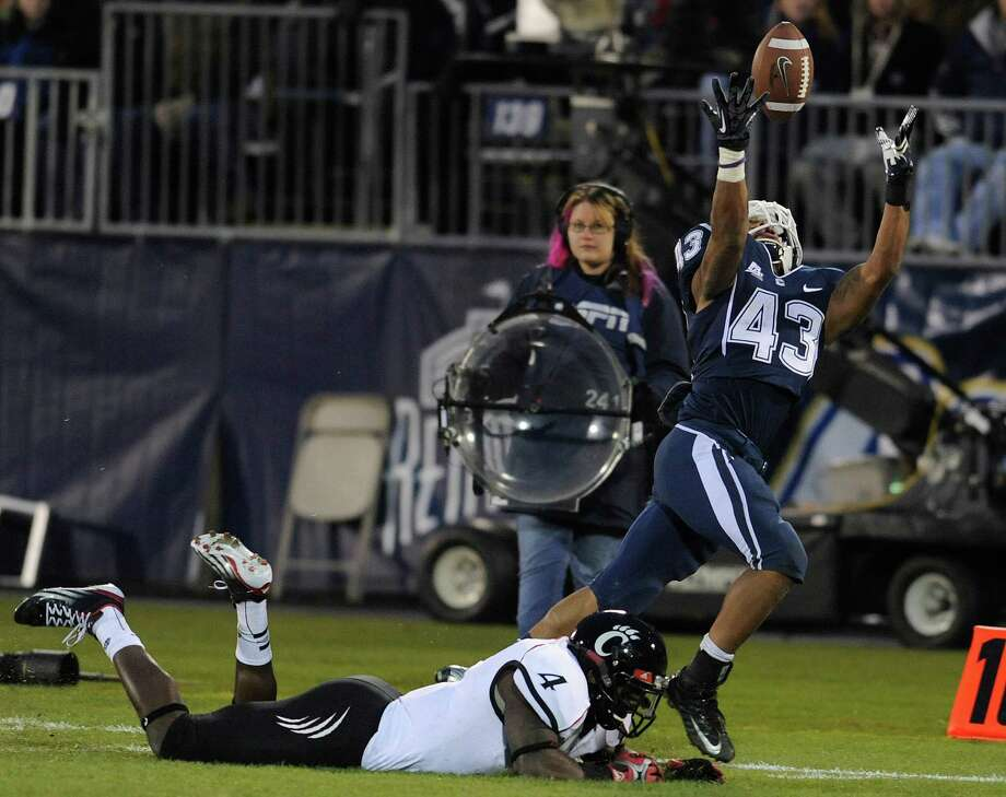 Connecticut running back Lyle McCombs (43) reaches for a pass while defended by Cincinnati linebacker Maalik Bomar (4) during the first half of an NCAA college football game at Rentschler Field in East Hartford, Conn., Saturday, Dec. 1, 2012.  The pass was incomplete. (AP Photo/Jessica Hill) Photo: Jessica Hill, Associated Press / FR125654 AP