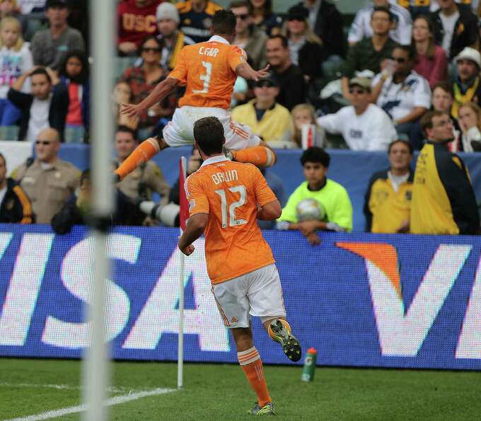 The Houston Dynamo's Calen Carr left, celebrates by jumping in the air after scoring a goal against