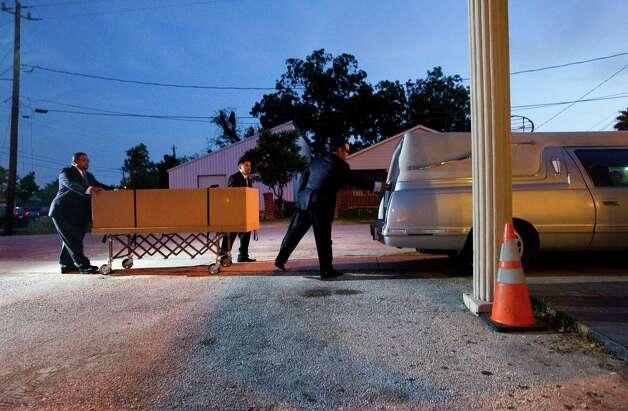 Funeral director Noe Santana, right, opens the hearse door ...