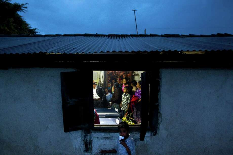 A young boy stands outside of the adobe house where the caskets of Leonel Tipaz de Leon, 21, below, and Diego Tipaz Jorge, 16, were placed for a vigil in August in their hometown of Piedras Blancas, Guatemala. The two were among 15 undocumented immigrants who died after an overloaded pickup truck carrying crashed outside of Goliad on July 22. ( Johnny Hanson / Houston Chronicle ) Photo: Johnny Hanson, Staff / © 2012  Houston Chronicle