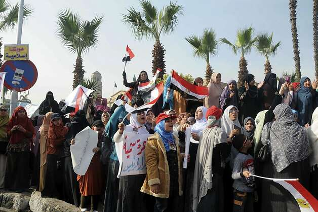Supporters of Egyptian President Mohammed Morsi rally in front of Cairo University, Cairo, Egypt, Saturday, Dec. 1, 2012. Tens of thousands of people waving Egyptian flags and hoisting large pictures of the president are demonstrating across Egypt Saturday in support of Morsi and Islamic law. The rally, organized by the Muslim Brotherhood, is seen as a test of strength for Islamists seeking to counteract large opposition protests held this past week by liberal and secular groups who the Brotherhood say do not represent the vast majority of Egyptians. (AP Photo/Mohammed Asad) Photo: Mohammed Asad, Associated Press