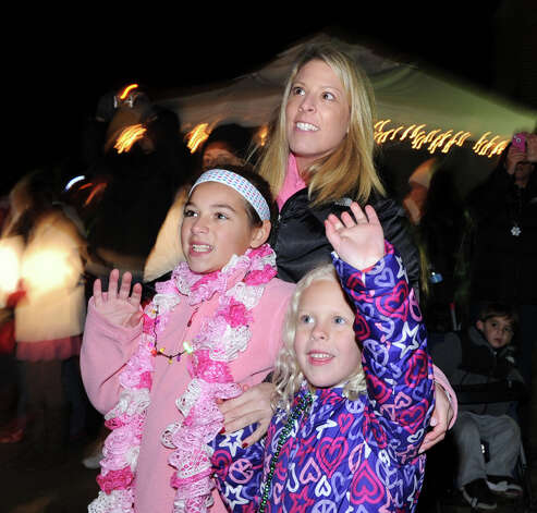 At top, Kris Bowling of Cos Cob, her daughter, Riley Bowling, 6, right, and Riley's cousin, Brady Wallace, 10, also of Cos Cob, wave to Santa during the first Winter's Eve Festival behind the Cos Cob Firehouse, Saturday, Dec. 1, 2012. Photo: Bob Luckey / Greenwich Time
