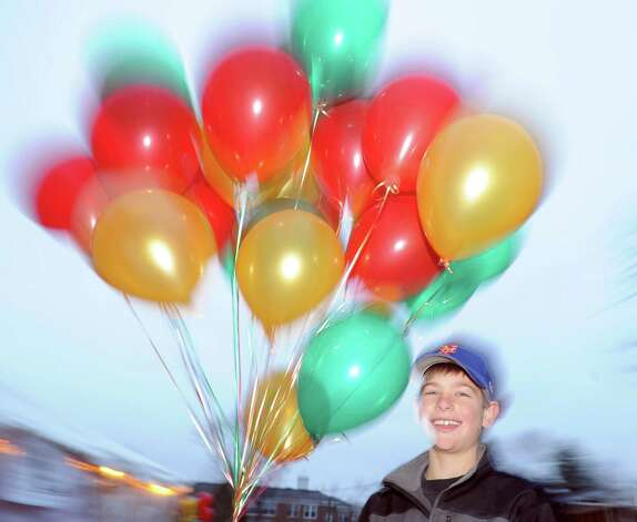 Andrew Scarlata, 10, of Cos Cob, holds a bunch of holiday balloons during the first Winter's Eve Festival behind the Cos Cob Firehouse, Saturday, Dec. 1, 2012. Photo: Bob Luckey / Greenwich Time