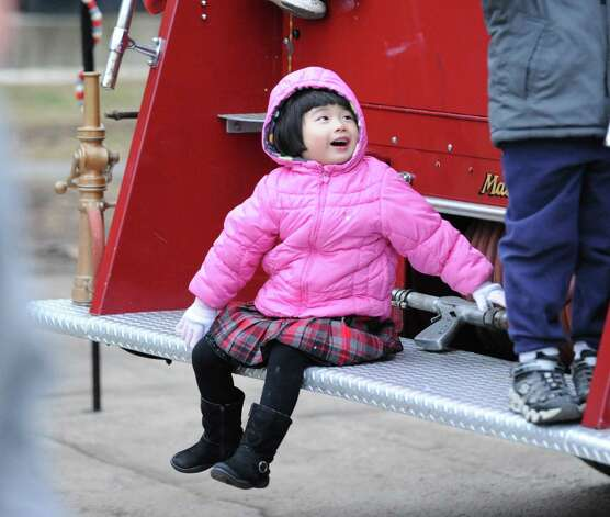 Enella Chen, 3, of Greenwich, smiles while sitting on the back of a 1947 Mack fire truck during the first Winter's Eve Festival behind the Cos Cob Firehouse, Saturday, Dec. 1, 2012. Photo: Bob Luckey / Greenwich Time