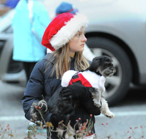 Juliet Freiheit, 10, of Cos Cob, wears a Santa hat as she carries her dog Leo during the first Winter's Eve Festival behind the Cos Cob Firehouse, Saturday, Dec. 1, 2012. Photo: Bob Luckey / Greenwich Time