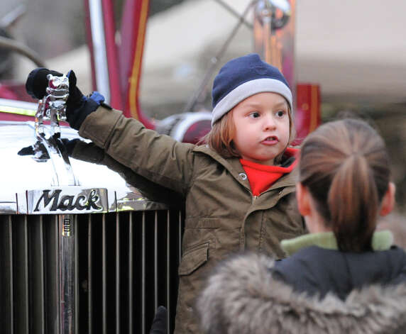 Sebastian Rose, 3, of Cos Cob, touches the Bulldog ornament on a 1947 Mack fire truck during the first Winter's Eve Festival behind the Cos Cob Firehouse, Saturday, Dec. 1, 2012. Photo: Bob Luckey / Greenwich Time