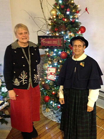 "Event creator Ann Watson, left, and decorator Phyllis Rodak greet visitors to ""The Festival of Trees, a Little Victorian Village Christmas,"" at the Round Lake Community Room, 49 Burlington Ave., Round Lake. The fundraiser for the village library features designer themed trees, table scapes, holiday decorations, and baked goods for purchase. Photo: Paul Block"
