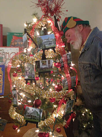 "Aaron Morris of Round Lake looks over one of the tabletop trees for sale at ""The Festival of Trees, a Little Victorian Village Christmas,"" on Saturday, Dec. 1, at the Round Lake Community Room. Photo: Paul Block"