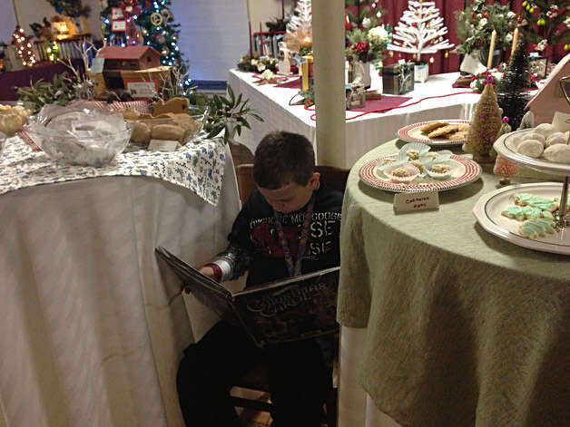 "Kaelan Kasowski, 9, of Malta, reads ""A Christmas Carol"" at ""The Festival of Trees, a Little Victorian Village Christmas,"" on Saturday, Dec. 1, at the Round Lake Community Room. Photo: Paul Block"
