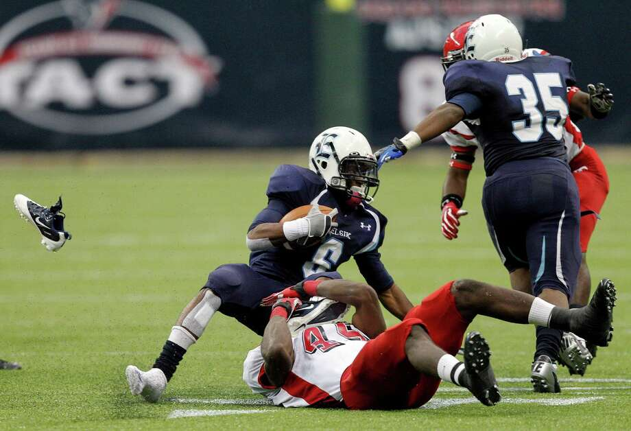 Elsik's Kaleb Cormier loses his shoe as he s brought down by North Shore's  Malik Hayward. Photo: Bob Levey, Houston Chronicle / ©2012 Bob Levey