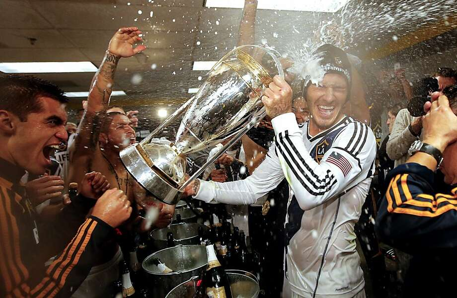 Los Angeles Galaxy's David Beckham, center, of England, is sprayed with champagne as they celebrate in the dressing room after defeating the Houston Dynamo 3-1 in the MLS Cup championship soccer game, Saturday, Dec. 1, 2012, in Carson, Calif.  (AP Photo/Jae C. Hong) Photo: Jae C. Hong, Associated Press