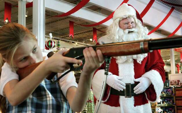 Santa Claus (also known as Jim Keithly, right), watches as Leah Freeman, 8, of St. Charles, takes aim with a laser air rifle game in Santa's Wonderland at Bass Pro Shops in St. Charles, Missouri. Photo: Robert Cohen, McClatchy-Tribune News Service / St. Louis Post-Dispatch