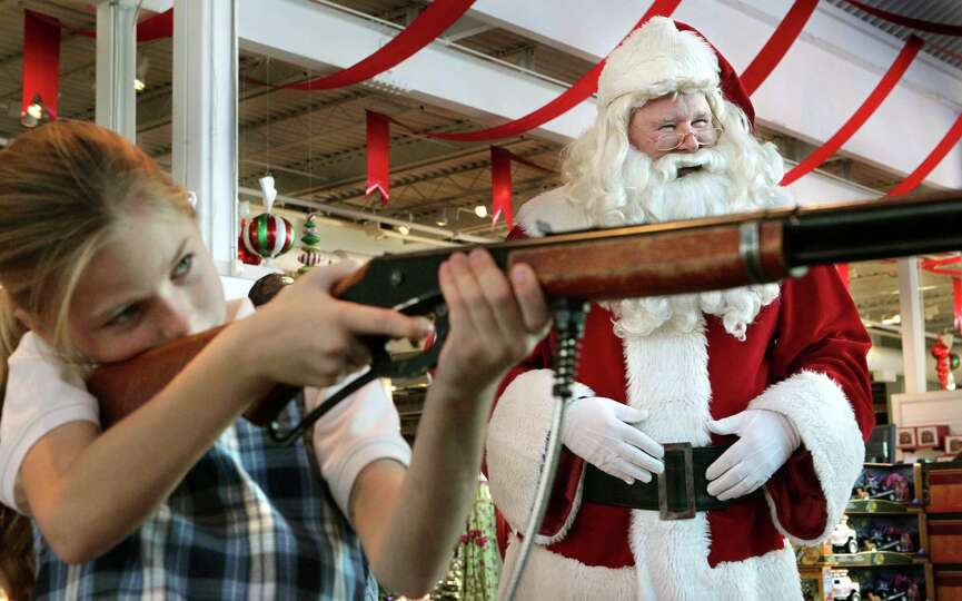 Santa Claus (also known as Jim Keithly, right), watches as Leah Freeman, 8, of St. Charles, takes ai