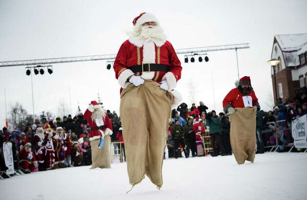 """Estonian Santa Claus """"Santa Aare"""" (L), Dutch Santa Claus """"Santa Holland"""" (C) and Swedish Santa Claus """"Snaretomten"""" compete in the Kicksled Sack Race during the Santa Clause Winter Games in Gallivare, above the polar circle in northern Sweden on November 17, 2012. Santas from all over the world gather this weekend for the Santa Claus Winter Games where they will practice """"Reindeer""""-ride, Porridge-eating, Santa-Karaoke, Kicksled Sack Race and Santas Christmas-eve. Photo: JONATHAN NACKSTRAND, AFP/Getty Images / AFP"""