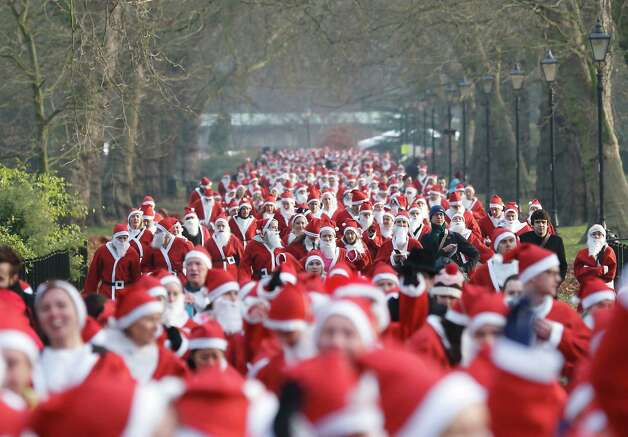 Charity runners dressed as Father Christmas participate in a 'Santa Run' charity fun run in Battersea Park in London on December 1, 2012. Hundreds of participants dressed in Santa suits and white beards ran through Battersea park in aid of winter sports charity Disability Snowsport in this 6km festive fun run. Photo: JUSTIN TALLIS, AFP/Getty Images / AFP