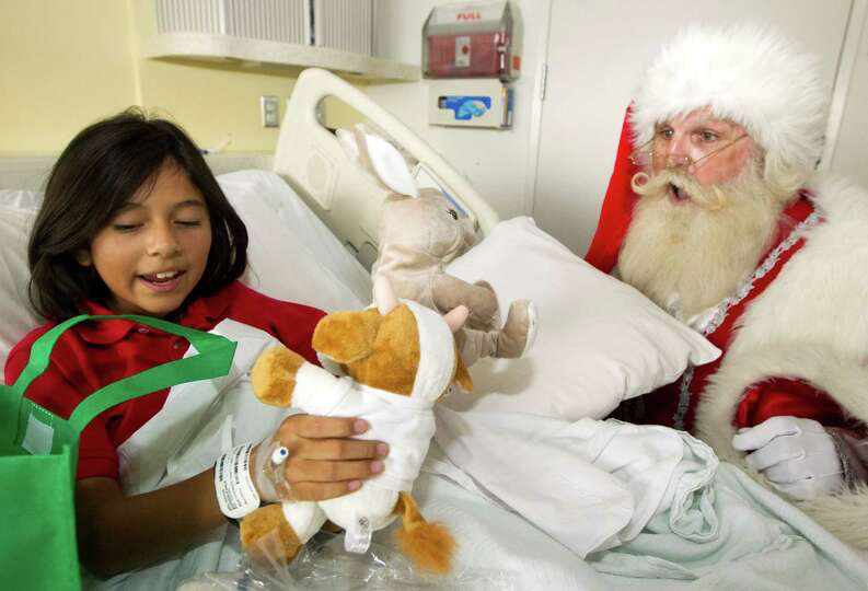 Santa Claus brings a gift to Karla Burden, 11, during a mini holiday parade through the hallways of