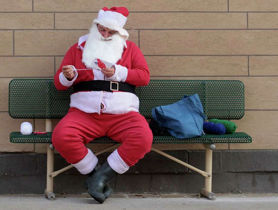 Dressed as Santa Claus, Robert Sapp, needleworks Christmas gifts on a bench Wednesday, Nov, 21, 2012, in downtown Quincy,  Ill.  Sapp said he was making toys to give away at  Christmas. Photo: Michael Kipley, Associated Press / AP