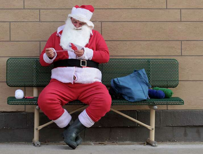 Dressed as Santa Claus, Robert Sapp, needleworks Christmas gifts on a bench Wednesday, Nov, 21, 2012