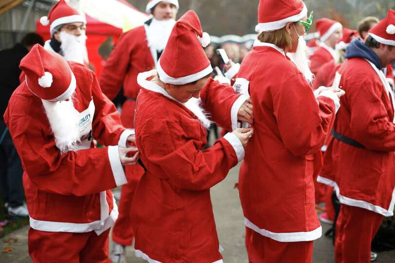Charity runners dressed as Father Christmas prepare to participate in a 'Santa Run' charity fun run