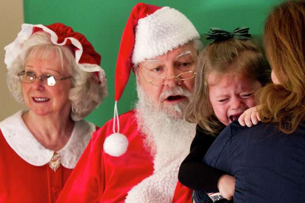 Cierra Spraggon holds on to her mother Alexcia while trying to have a photo taken with Santa and Mrs. Claus at Sugar Land Town Square Sunday, Nov. 25, 2012, in Sugar Land. The free photos will be offered on Sundays through December 16. Photo: Brett Coomer, Houston Chronicle / © 2012 Houston Chronicle