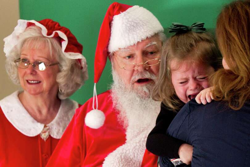 Cierra Spraggon holds on to her mother Alexcia while trying to have a photo taken with Santa and Mrs