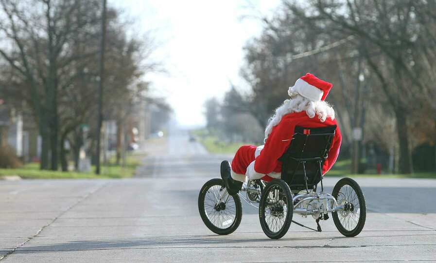 Santa Claus rides a recumbent bicycle along a quiet street in Jefferson, Iowa, while promoting the G