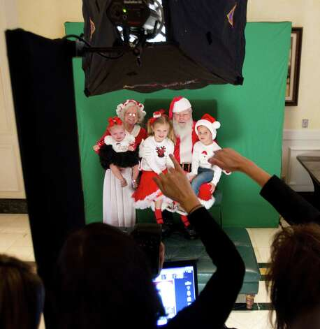 Bella, Emily and Victor Zaccardo pose for photos with Santa and Mrs. Claus at Sugar Land Town Square Sunday, Nov. 25, 2012, in Sugar Land. The free photos will be offered on Sundays through December 16. Photo: Brett Coomer, Houston Chronicle / © 2012 Houston Chronicle