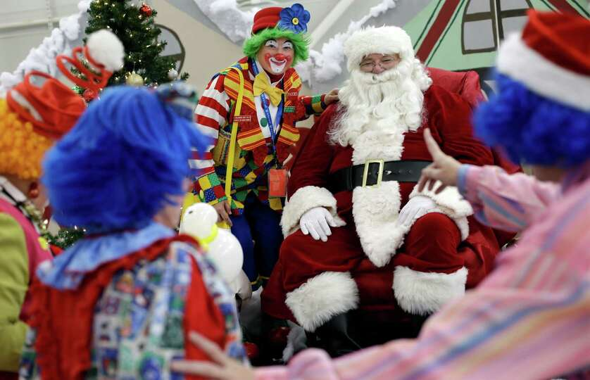 A group of clowns take turns posing for photos with Santa Claus at