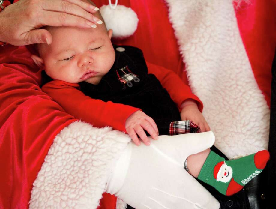 Benjamin Curtis sleeps in Santa's arms while having Christmas pictures taken at Sugar Land Town Square Sunday, Nov. 25, 2012, in Sugar Land. The free photos will be offered on Sundays through December 16. Photo: Brett Coomer, Houston Chronicle / © 2012 Houston Chronicle