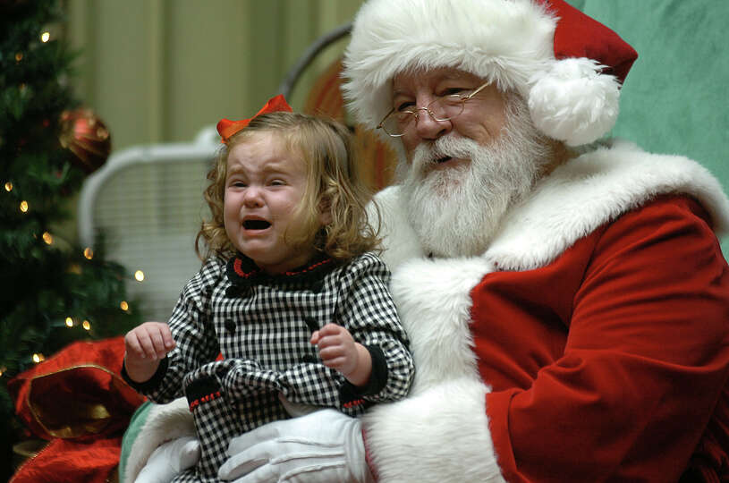 Rose Morrison, 2,  of Scranton, Pa. cries as she sits with Santa Claus for a holiday portrait on Wed
