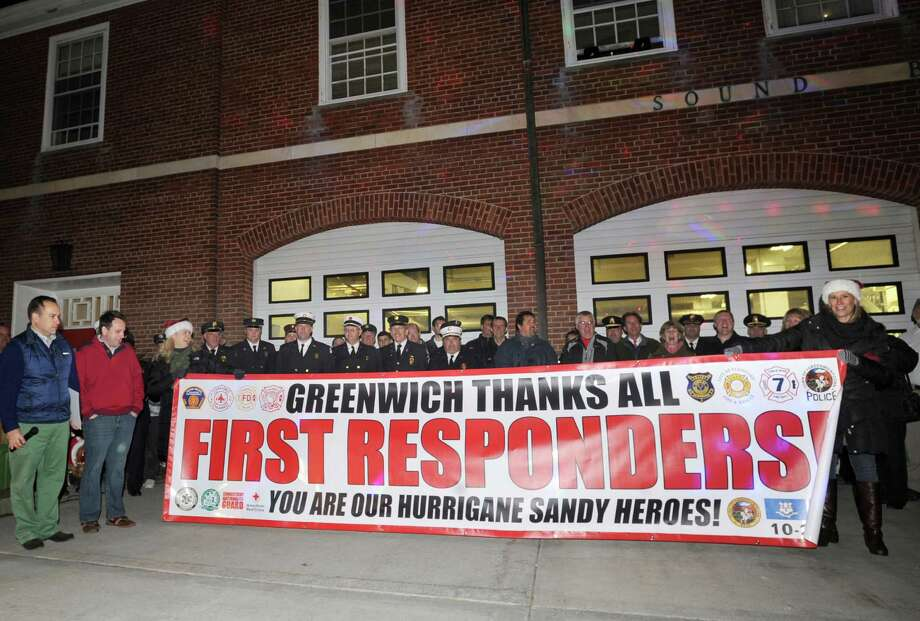 Greenwich First Selectman Peter Tesei, left, and Selectman Drew Marzullo, second from left, watch as a thank you banner is displayed during an Old Greenwich Community appreciation ceremony for first responders and emergency personnel for their work before, during and after Hurricane Sandy, at the Sound Beach Firehouse, Saturday night, Dec. 1, 2012. Photo: Bob Luckey / Greenwich Time