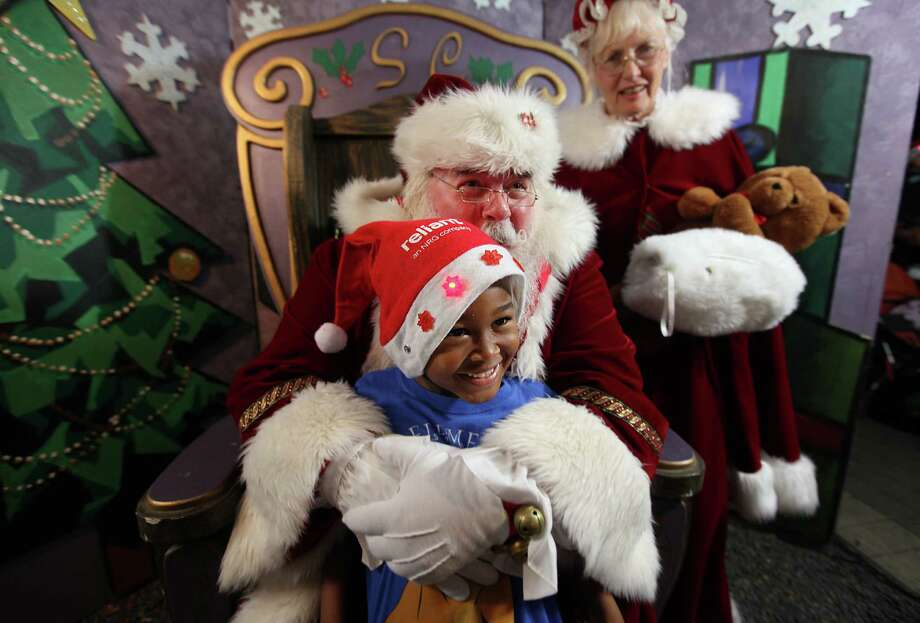 Tyler Darden,3, smiles as Santa squeezes him tight while getting ready to take a photo during the Mayor's 2012 Holiday Celebration and Tree Lighting at City Hall on Friday, Nov. 30, 2012, in Houston.  Over 10,000 Houstonians are expected to ring in the season by lighting the 63-Foot White Fir Holiday Tree. Photo: Mayra Beltran, Houston Chronicle / © 2012 Houston Chronicle