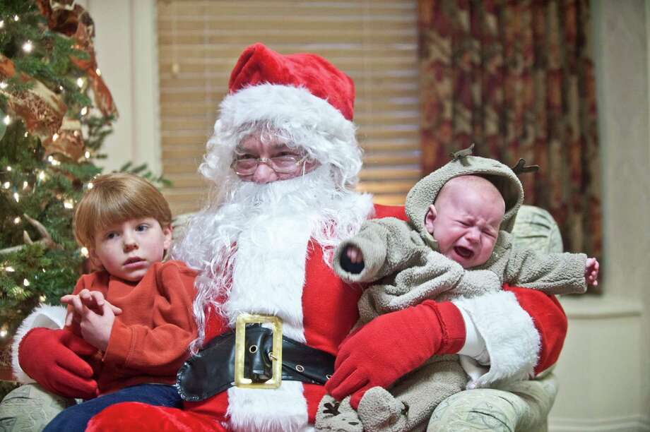 Four-year old Rigdon Anderson, left, and four-month old Arnold Anderson get their photo taken with a man portraying Santa Claus at a bank in Danville, Ky. on Saturday, Nov. 24, 2012. Photo: Clay Jackson, Associated Press / The Advocate Messenger