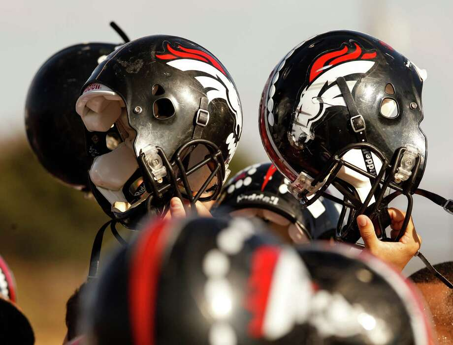 Spring Westfield players raise their helmets after a huddle before taking on Skyline in the Class 5A Division I Region II semi-finals. Photo: Stan Olszewski, Staff Photographer / Stan Olszewski/The Dallas Morning News